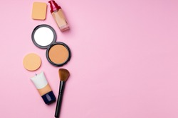 Complexion make up products and brush on pink background