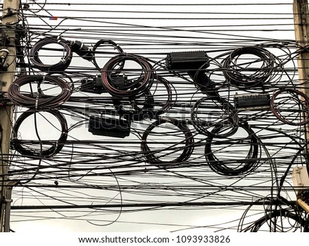 Complicated of telephone wires and Fibre Optice cables on electric pole.(Mobile Photography) #1093933826