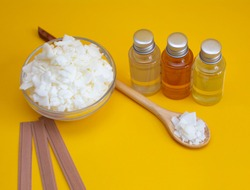 Components for making candles with your own hands. The photo shows wooden wicks, soy wax, holders, and oil flavorings on a yellow background.
