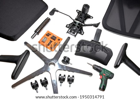 Components of an office chair. Closeup of a complete set of spare parts for assembly of an computer or office chair and a cordless drill for the construction isolated on a white background. Stockfoto ©