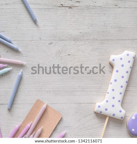 Components to decorate the birthday party treats flat lay. Royal icing topper cookie for cake in form of number one, candles, cards on a light wooden background. Soft focus, pastel colors.