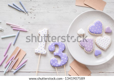Components to decorate the birthday party treats. Royal icing cookies, candles, cards on a light wooden background. Soft focus, pastel colors, numbers 13 and hearts, top view.