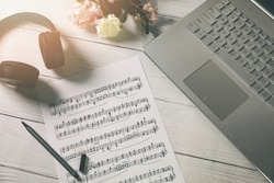 compose music and education - paper sheet with musical notes, laptop and headphones on the artist desk