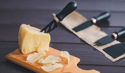 Composed cloesup detail view of aged cheddar cheese with cheese knife set, over vintage brown wooden backdrop