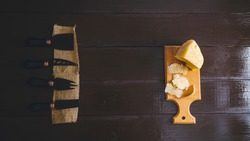 Composed Flat lay detail view of aged cheddar cheese with cheese knife set, over vintage brown wooden backdrop with copy space