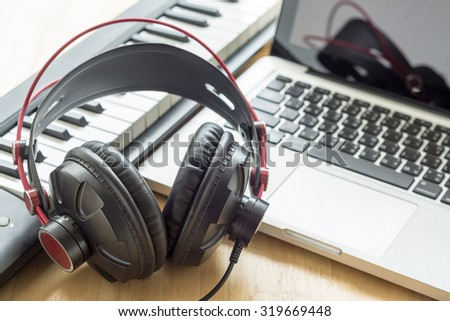 Composer workplace. Headphones, keyboard and a laptop. Computer music concept.