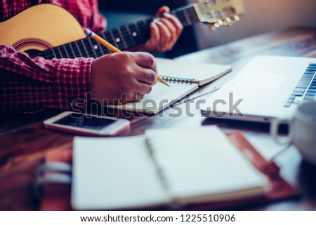 Composers are writing songs on the table with guitars. #1225510906