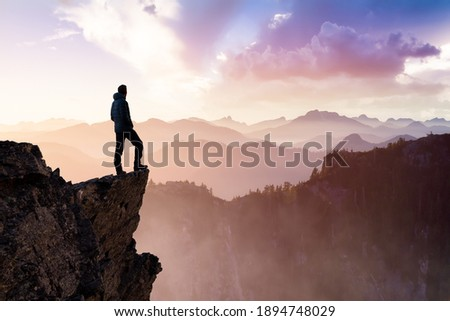Composite. Adventurous Man Hiker With Hands Up on top of a Steep Rocky Cliff. Sunset or Sunrise. Landscape Taken from British Columbia, Canada. Concept: Adventure, Explore, Hike, Lifestyle Foto stock ©