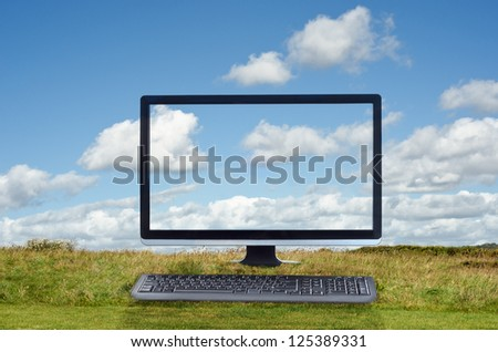 Composite image of a cloud computing concept.  Monitor and keyboard facing front and positioned on grass with blue sky and white fluffy clouds in the background.  Clouds pass across the screen.