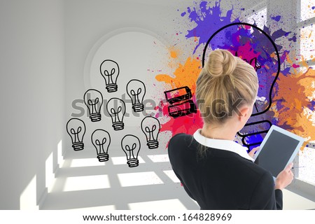Composite image of blonde businesswoman holding new tablet
