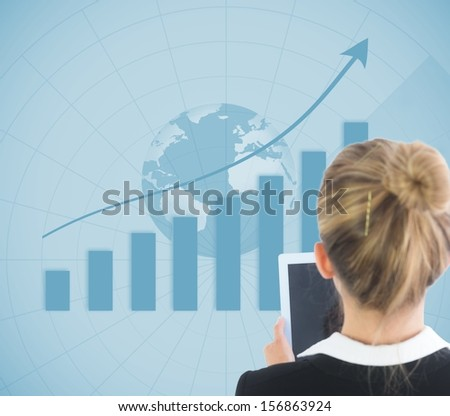 Composite image of blonde businesswoman holding tablet in front of blue global background showing statistic