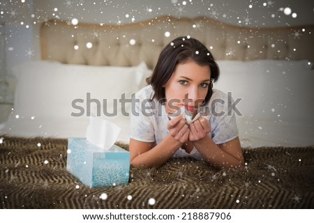Composite image of calm pretty brown haired woman sneezing in a tissue against snow