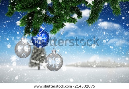 Composite image of christmas decorations against fir tree in snowy landscape