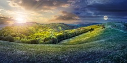 composite image of day and night concept of Idyllic view of pretty farmland rolling hills. Rural landscape near the forest in mountains.
