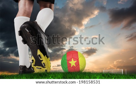 Composite image of football boot kicking cameroon ball against green grass under blue and orange sky