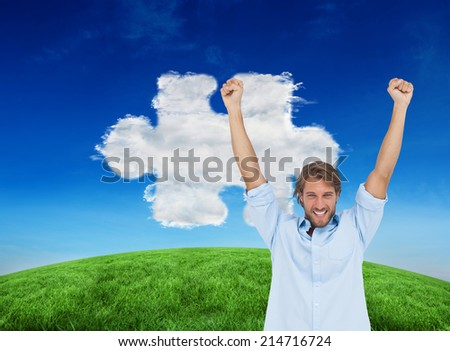 Composite image of happy man celebrating success with arms up against cloud jigsaw piece
