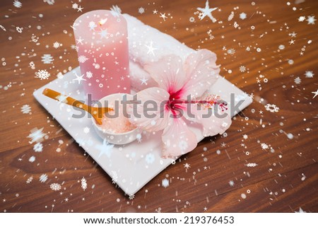 Composite image of snow against spa objects on wooden floor