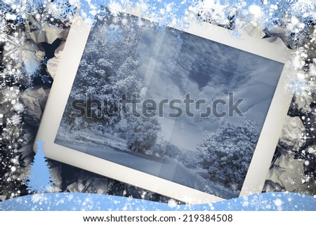 Composite image of tablet screen against snow flake frame in blue