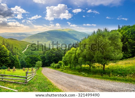 composite landscape. fence near road going down the hill through meadow and forest to the high mountains in morning light