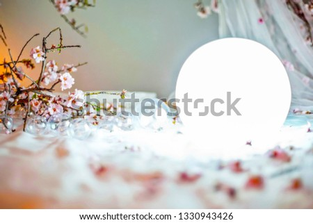 Composition background of blossoming almond branches, delicate transparent organs, transparent balls of various sizes and a luminous ball against the background of a light wall of pastel color.CloseUP #1330943426