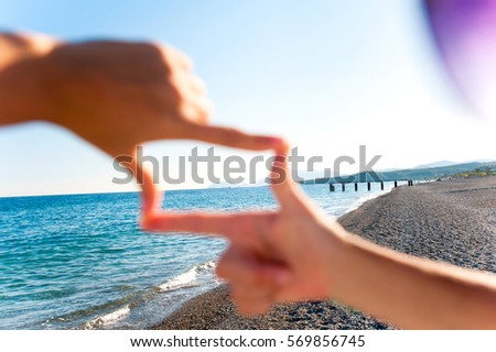 Composition finger frame- girl's hands capture spectacular seascape horizon on the beach at sunset. Vibrant multicolored horizontal outdoors image with copy space on blue sky background.