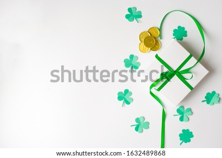 Composition for St. Patrick's Day. Gift white box with a green satin bow, clover and toy gold coins on a white background. The view from the top, lay flat, copy space