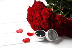 Composition from a bouquet of beautiful red roses and a gift jewelry box on the background. Valentine's day gift.