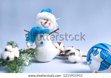 composition in blue, snowman, green spruce branch, cotton branch, blue Christmas ball, on a blue background, Christmas decor