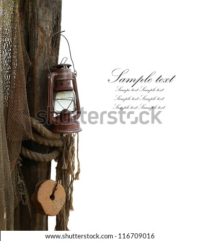 composition is marine consisting of an old lamp, rope and fishing net isolated in white