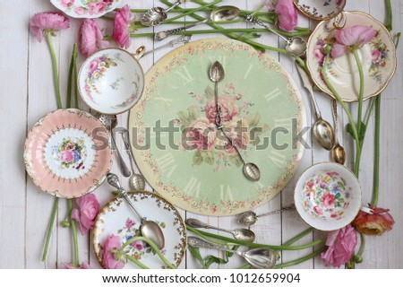 Composition made from old clock face and spoon, five-oçlock tea, collection of authentic  silver-plate spoon, fresh flowers, bone china, porcelain vintage tea cup and saucer