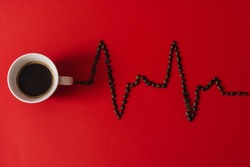 Composition made of coffee cup and coffee beans arranged in heartbeat pattern on a red background. MInimal flat lay.