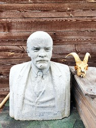 composition of a bust of V. I. Lenin and a goat skull on a box, against the background of a wooden shed in a Russian village Echoes of the past of the former Union of Soviet Socialist Republics