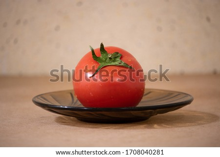 composition of a red tomato, round shape on a black saucer, still life. Сток-фото ©