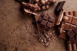 Composition of bars and pieces of different milk and dark chocolate, grated cocoa on a brown background top view close up