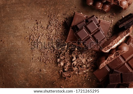 Photo of  Composition of bars and pieces of different milk and dark chocolate, grated cocoa on a brown background top view close up