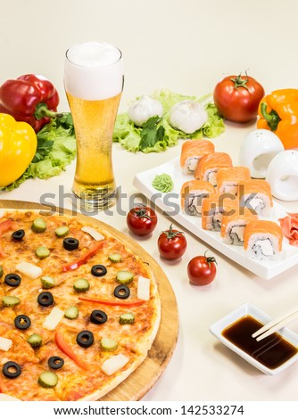 composition of beer sushi  and pizza on white background
