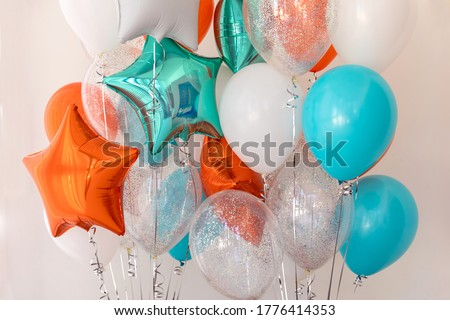 Composition of blue, silver, orange and transparent balloons with helium. Foil balloon in the shape of a star. The concept of decorating a room with helium balloons for holidays or birthdays