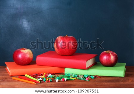 Composition of books, stationery and an apples on the teacher\'s desk in the background of the blackboard