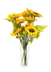 Composition of bright artificial sunflowers in glass vase isolated on white background. Closeup.