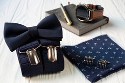 Composition of business accessories for men in vintage style - bow tie, suspenders, handkerchief and cufflinks.