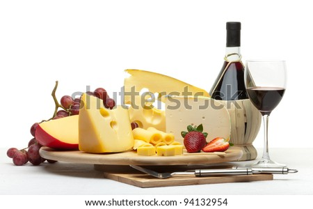 Composition of cheese, grapes, bottles and glasses of wine and strawberries on a wooden round tray on a white tablecloth, isolated on a white background