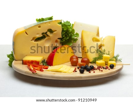 Composition of cheese on a wooden round tray on a white tablecloth, isolated on a white background