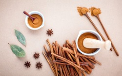 Composition of cinnamon stick and cinnamon powder in white mortar with star anise ,bay leaves and wooden spoon on brown background .
