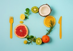 Composition of citrus fruit, orange and lemon, coconut, kiwi on cyan background