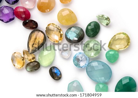 Composition of colorful precious gems on the white background. Many different colors and shapes. Citrine, amethyst, ruby, emerald, blue topaz, labradorite, garnet, moonstone, rose quartz and more.