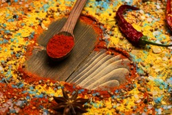 Composition of condiment making heart shape. Food art concept. Wood spoon with paprika, red chili pepper, anise star, sea salt and scattered seasoning. Set of spices on wooden background.