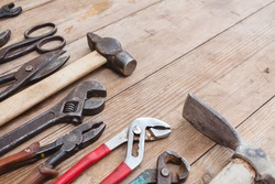 Composition of construction tools on an old battered wooden surface: pliers, pipe wrench, screwdriver, hammer, metal shears, saws