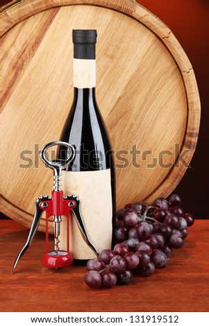 Composition of corkscrew and bottle of wine, grape, wooden barrel  on wooden table on dark background