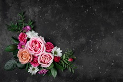 Composition of delicate summer flowers on a black background top view, free space for text. Bouquet of pink roses and white daisies