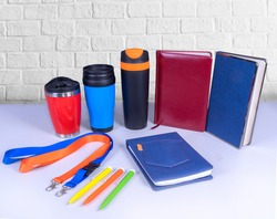 Composition of different promo products -Thermo mugs, Lanyards Neck Strap, pens, notebooks for business. On desk grey and background white wall